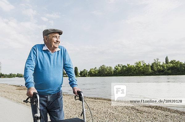Lächelnder älterer Mann beim Spaziergang mit Radwanderer am Flussufer