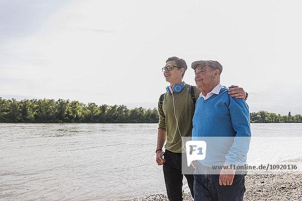 Großvater und Enkel stehen am Flussufer und schauen gemeinsam in die Ferne.