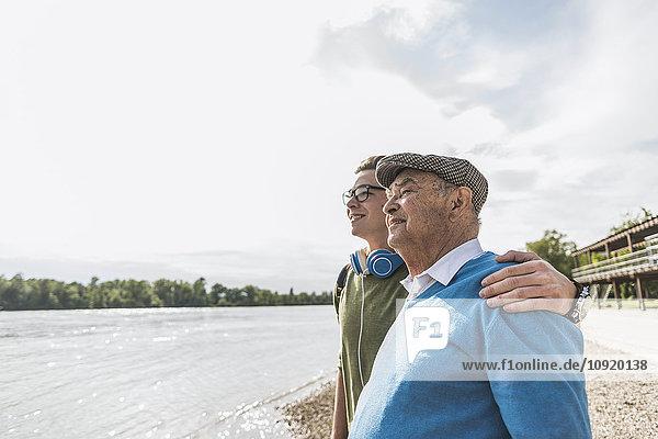 Großvater und Enkel am Flussufer schauen gemeinsam in die Ferne