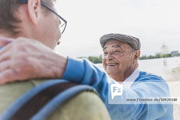 Porträt eines lächelnden älteren Mannes mit seinem Enkel