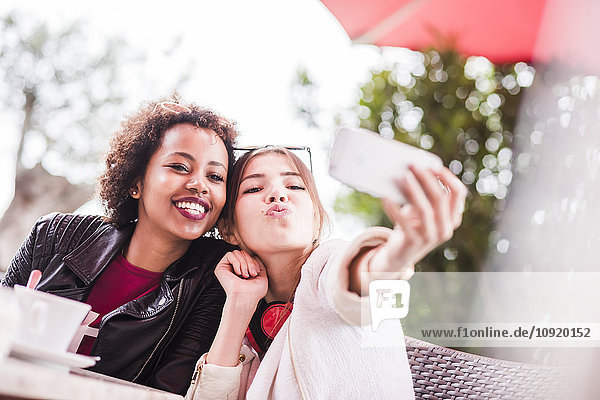 Two best friends taking selfie with smartphone