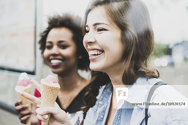 Laughing woman with icecream cone and friend in the background