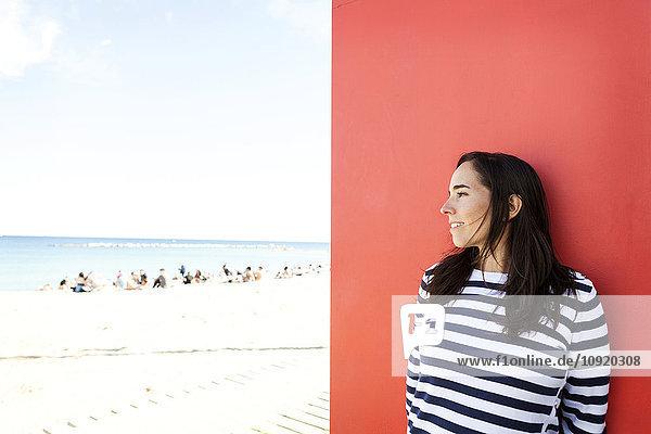 Spanien  Barcelona  Frau in gestreiftem Pullover an der roten Wand lehnend  zum Strand schauend