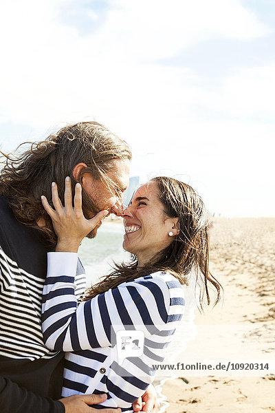 Spanien  Barcelona  glückliches Paar  das sich am Strand die Nase reibt