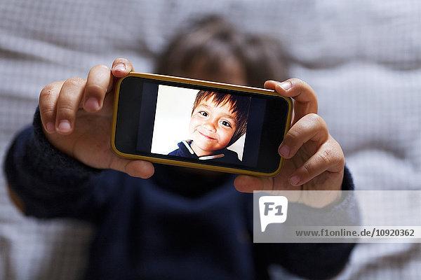 Kleiner Junge  der ein Handy mit Bild von sich hält