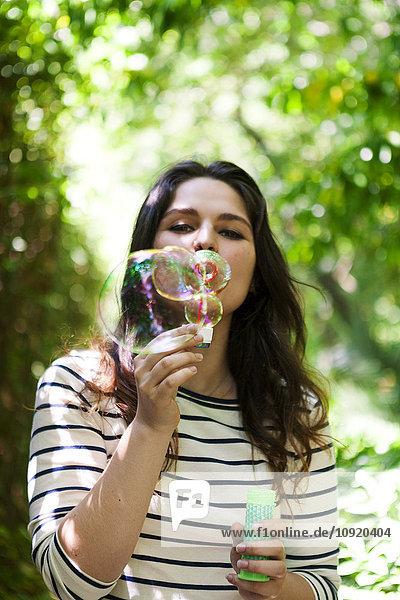 Junge Frau bläst Seifenblasen