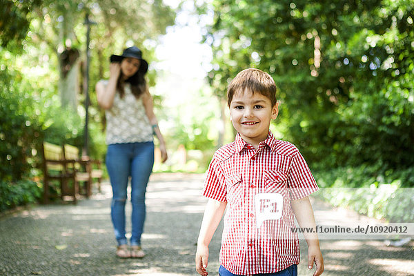 Boy in park with mother in background