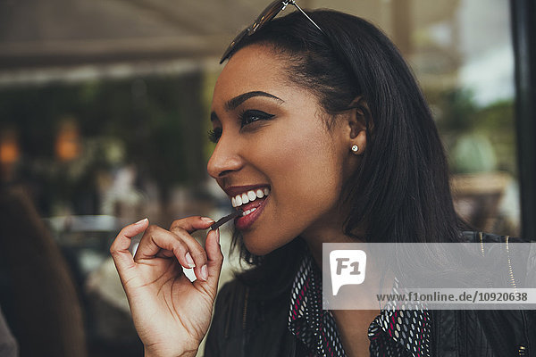 Portrait of smiling young woman eating chocolate in a cafe