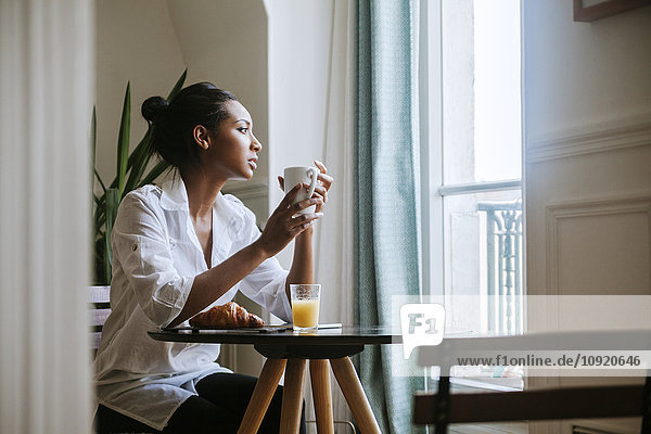 Junge Frau beim Frühstück mit einer Tasse Kaffee und Blick durchs Fenster