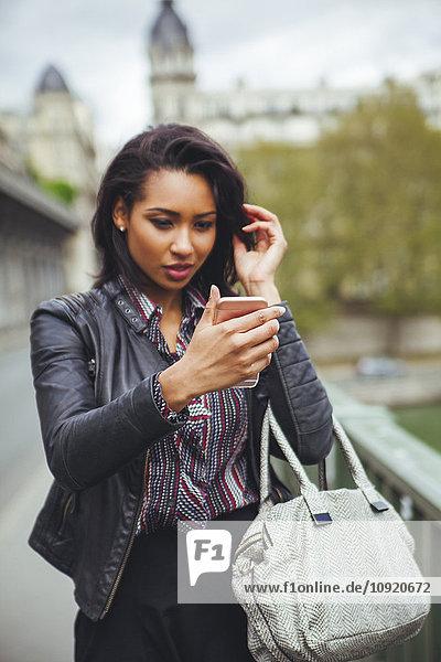 Frankreich  Paris  junge Frau beim Blick auf Smartphone