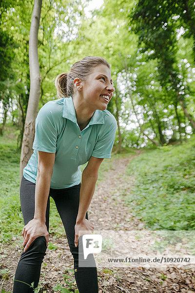 Lächelnde Sportlerin ruht im Wald
