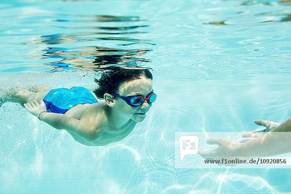 Kleiner Junge taucht zur Mutter  unter Wasser  Schwimmbad