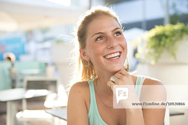 Portrait of happy young woman at outdoor cafe in summer