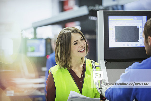 Lächelnder Supervisor und Arbeiter am Schaltschrank im Stahlwerk