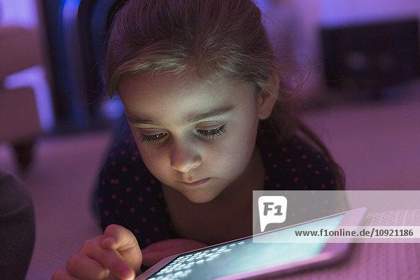 Nahaufnahme Mädchen spielen Spiel auf digitalem Tablett im Dunkeln