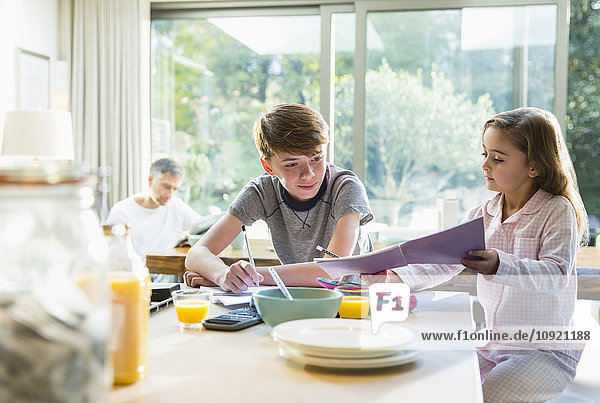 Bruder und Schwester beim Frühstücken und Hausaufgaben machen