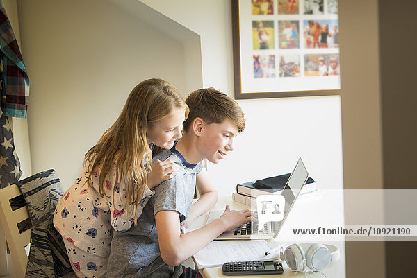 Sister watching brother using laptop in bedroom