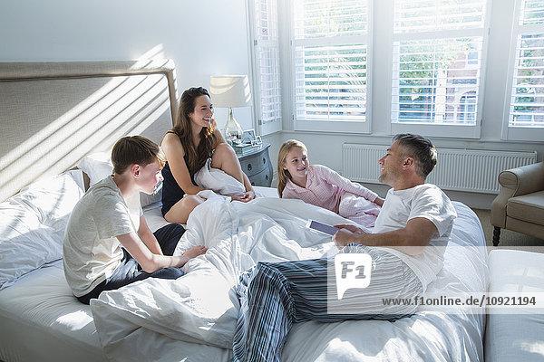 Familie im Pyjama entspannt auf dem Bett