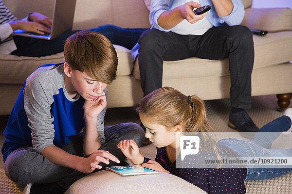Bruder und Schwester teilen sich ein digitales Tablett im Wohnzimmer