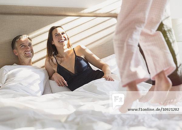 Lächelnde Eltern beobachten Kinder beim Springen auf dem Bett