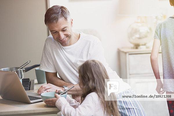 Vater und Tochter beim Frühstück am Laptop
