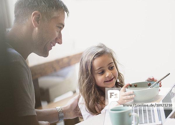 Vater und Tochter beim Frühstücken am Laptop