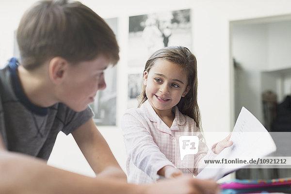 Stolze Schwester mit Hausaufgaben für den Bruder