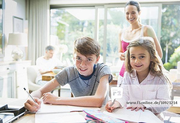 Porträt lächelnde Geschwister bei den Hausaufgaben