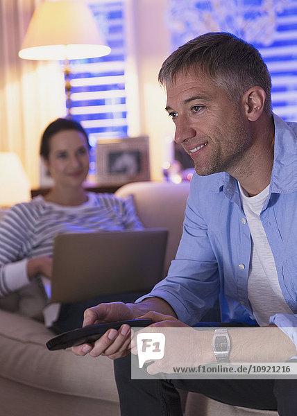 Frau mit Laptop und Mann beim Fernsehen im Wohnzimmer