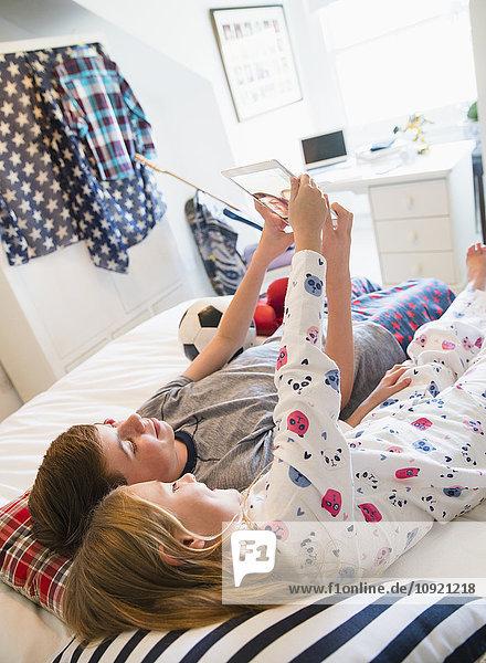 Bruder und Schwester nehmen Selfie auf Bett mit digitaler Tablettkamera