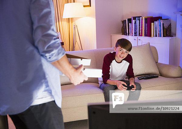 Vater bringt Pizza zum Sohn und spielt ein Videospiel im Wohnzimmer.