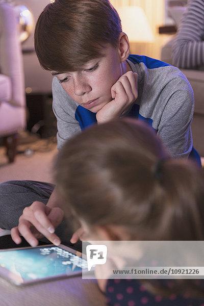 Bruder und Schwester spielen Videospiel auf digitalem Tablett