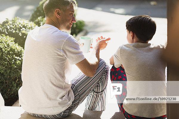 Vater mit Kaffee im Gespräch mit dem Sohn auf der Vordertreppe
