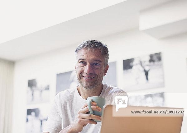 Lächelnder Mann trinkt Kaffee am Laptop