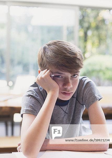 Porträt des gelangweilten Jungen bei den Hausaufgaben
