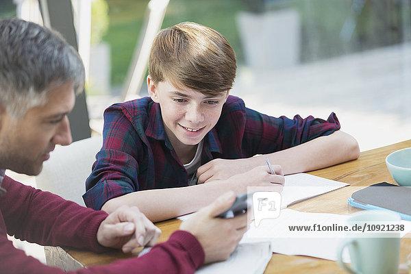 Vater mit Taschenrechner hilft Sohn bei Mathe-Hausaufgaben