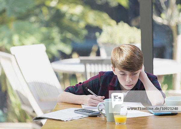 Junge macht Mathe-Hausaufgaben am Esstisch