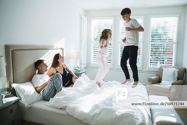 Eltern beobachten Kinder beim Springen auf dem Bett