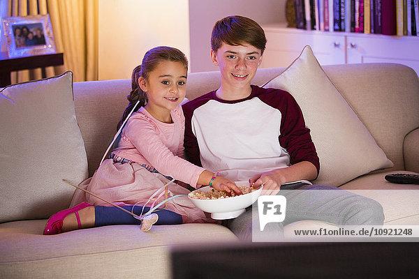 Geschwister essen Popcorn und Fernsehen im Wohnzimmer