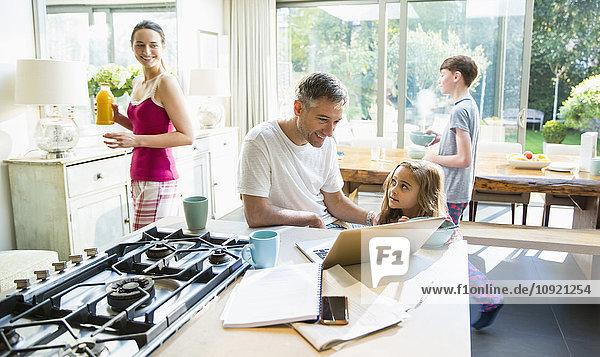 Familie mit Frühstück und Laptop in der Morgenküche