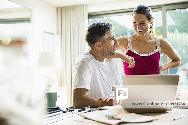 Lächelndes Paar am Laptop in der Morgenküche