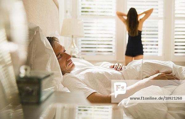 Frau streckt sich am Morgenfenster hinter dem Mann  der im Bett schläft.
