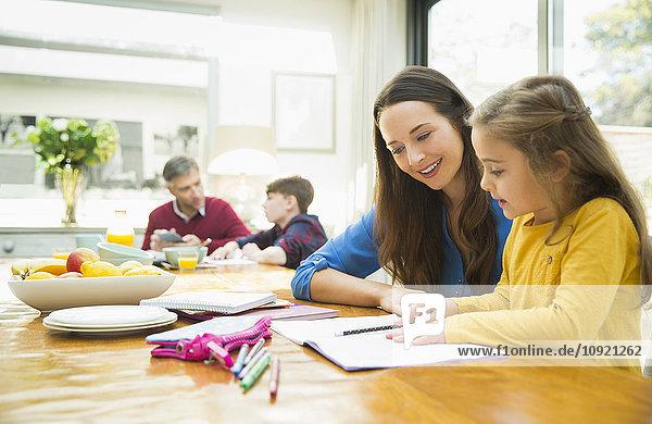 Mutter und Tochter machen Hausaufgaben am Esstisch