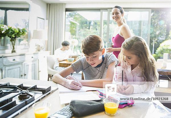 Mutter beobachtet Bruder und Schwester bei den Hausaufgaben an der Küchenzeile.