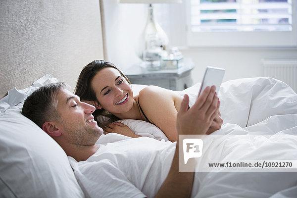 Lächelndes Paar  das mit einem digitalen Tablett im Bett liegt.