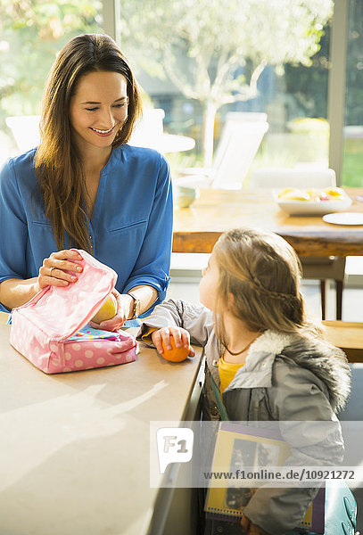 Mother packing lunch for daughter in kitchen