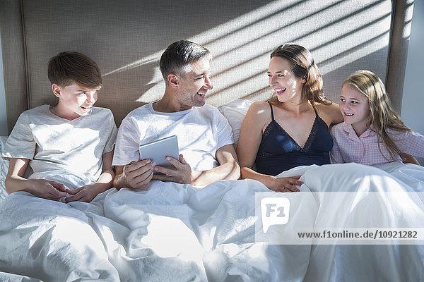 Lächelnde Familie im Bett liegend mit digitalem Tablett