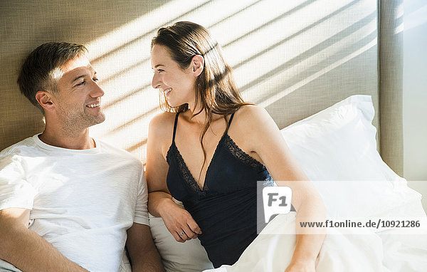 Lächelndes Paar im Bett sprechend