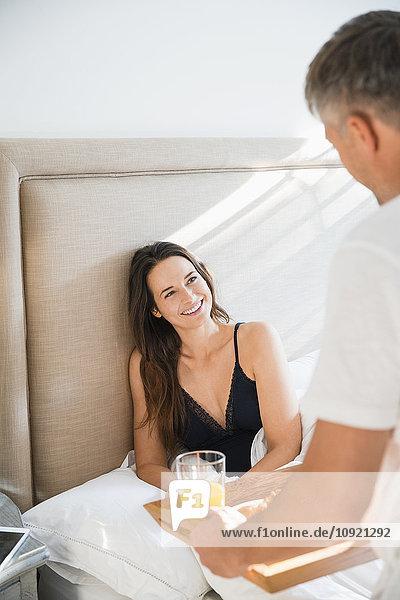 Frau lächelt den Mann an  der das Frühstück im Bett serviert.