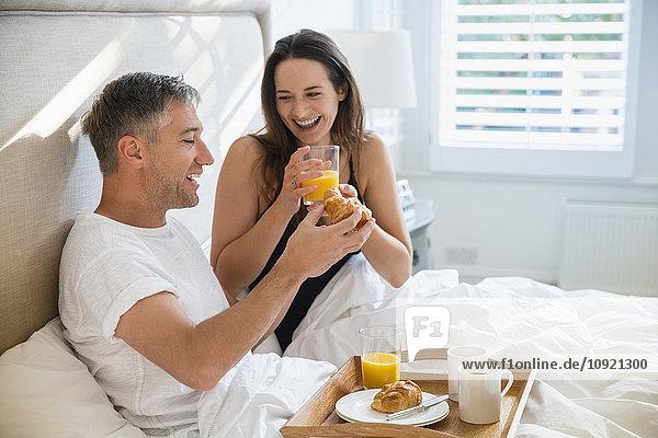 Lächelndes Paar beim Frühstück im Bett